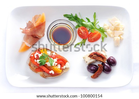 Variety of canapes on a plate; olives and sundried tomato, parma ham with rockmelon, toast with roasted mixed peppers and feta cheese, cubes of cheese and salad - stock photo