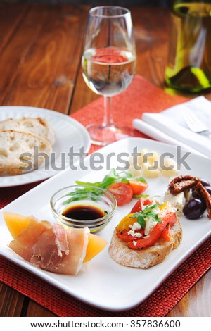 Variety of canapes on a white platter served with bread and wine  - stock photo