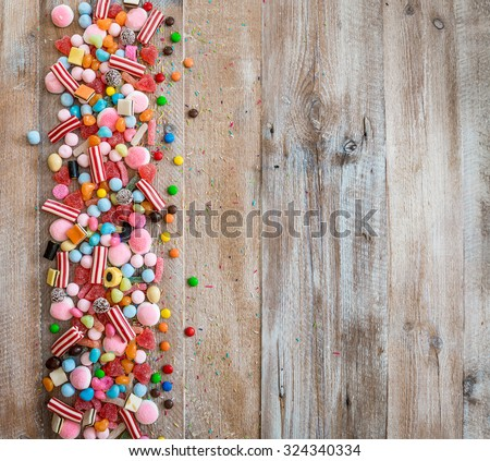 variety of candies on a wooden background with space for text - stock photo