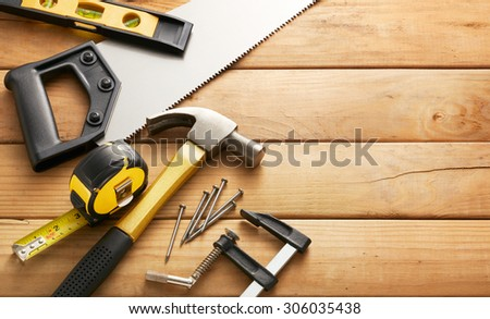 variety of carpentry tools on wood planks with copy space - stock photo