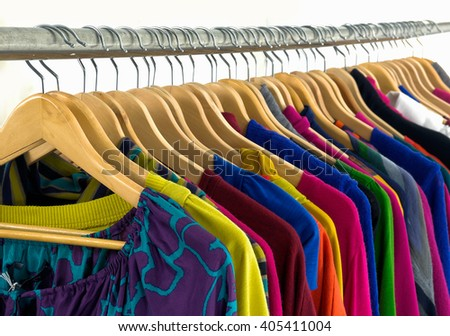 Variety of casual female clothes of different colors on hangers - stock photo