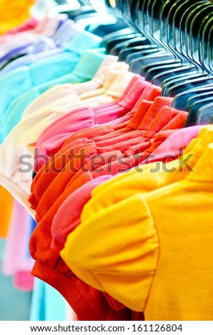 Variety of casual  T-shirts on hangers . Focus Orange T-Shirts .