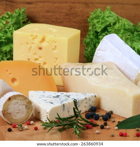 Variety of cheese: ementaler, gouda, Danish blue soft cheese and other hard cheeses. Herbs and spices. - stock photo