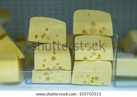 Variety of cheeses  pieces on shelves in supermarket