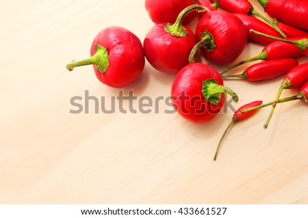 Variety of chili peppers over wooden table background