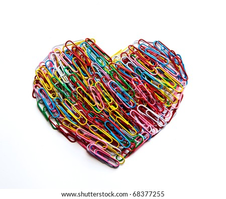 Variety of color paper clips arranged in heart shape on isolated white background. - stock photo