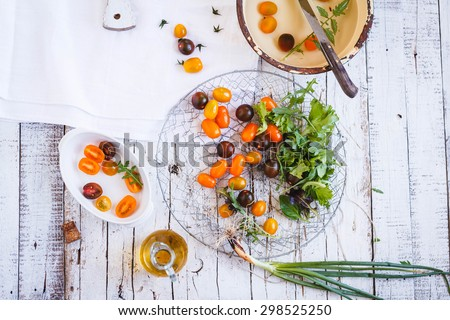 Variety of Colored fresh cherry tomato served in metallic basket over on a rustic white wooden table from above. Rustic composition of styling.  - stock photo