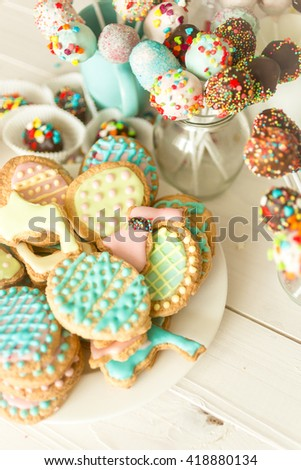 Variety of colorful cake pops and cookies on white wooden desk - stock photo