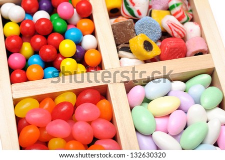 variety of colorful candy in wooden case