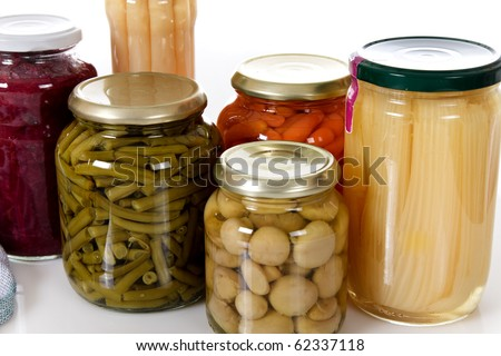 Variety of colorful canned vegetables in glass pot. Food, preserve concept. Studio shot. White background. - stock photo
