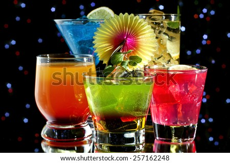 Variety of colorful cocktails over starry black background - stock photo