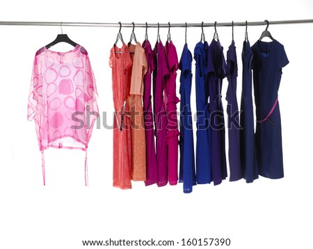 Variety of colorful female clothing hanging on hangers