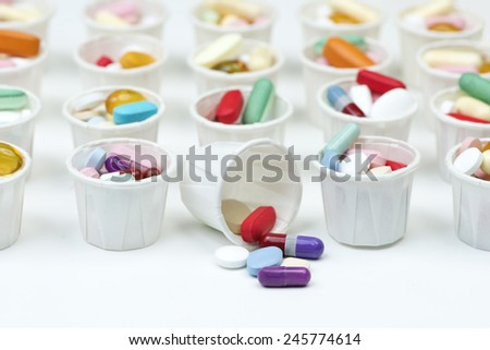 Variety of colorful pills arranged in white paper medication cups. - stock photo
