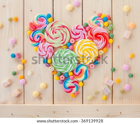 Variety of colorful popsicles and candy in a heart shape