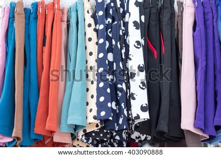 Variety of colorful women clothing hanging on rail in fashion shop , vintage clothes hanging in the flea market of used things - stock photo