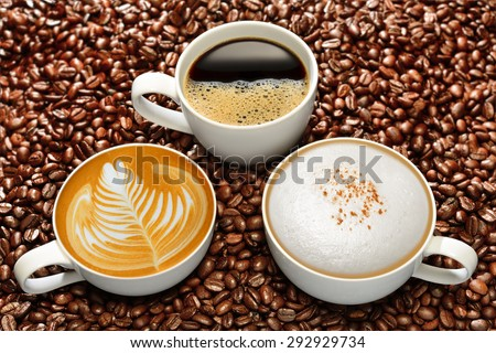 Variety of cups of coffee on coffee beans background - stock photo