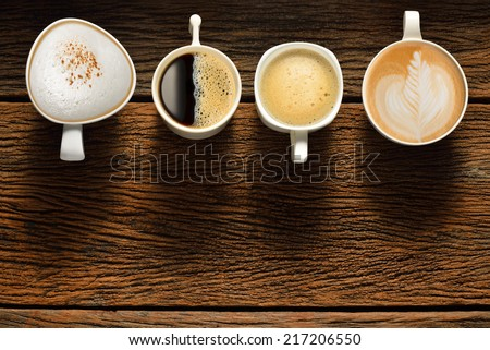 Variety of cups of coffee on old wooden table - stock photo