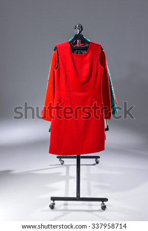 Variety of different clothes for females rack display-light background - stock photo