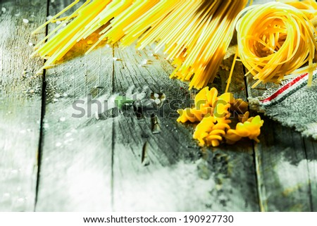 Variety of different Italian dried pasta ingredients arranged in the corner on rustic weather wooden boards with copyspace including spaghetti, fusilli , tagliatelli and linguini - stock photo