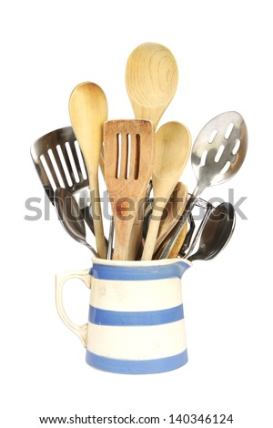 Variety of different kitchen utensils in a blue and white striped jug
