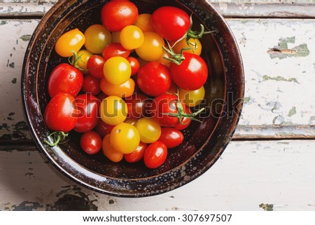 Variety of different tomatoes: red, orange, yellow and cherry freshly washed in a black bowl
