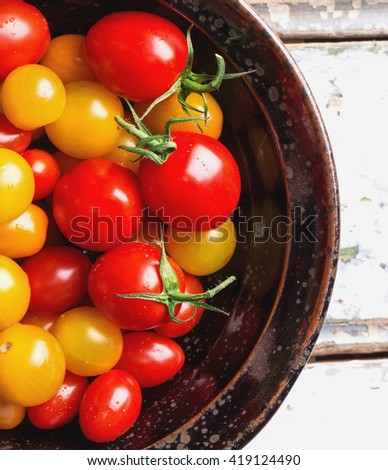 Variety of different tomatoes: red, orange, yellow and cherry freshly washed in a black bowl - stock photo
