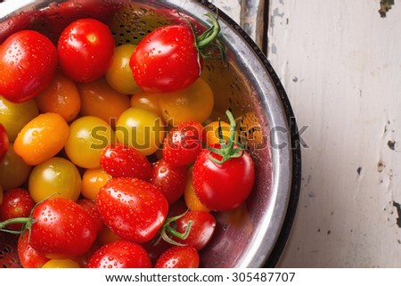 Variety of different tomatoes: red, orange, yellow and cherry freshly washed in colander