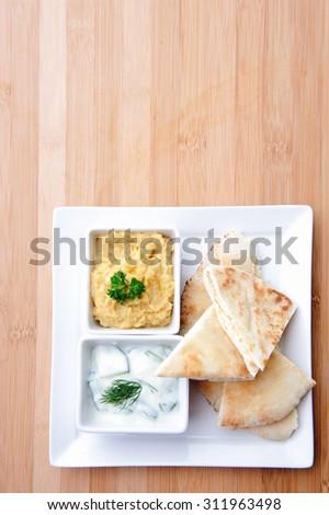 Variety of dips with flatbread; Tzatziki and humus/hummus - stock photo