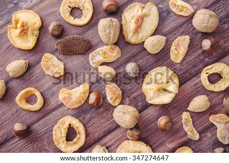 Variety of dried fruits (peaches, mandarins, tangerines, apples) and nuts (walnuts, hazel nuts, almonds and Brazilian nuts) scattered on wooden background
