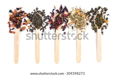 Variety of dry tea leaves scattered over spoons on white background