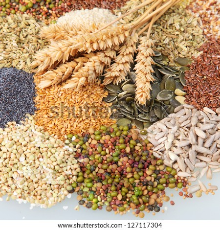 Variety of edible seeds with ripe ears of wheat includomg whole and dehusked sunflower, sesame, poppy, linseed, pulses and legumes