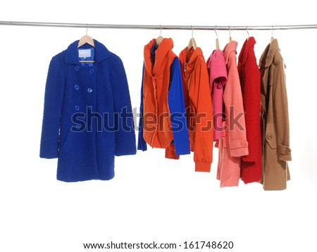 Variety of female coat and clothing hanging on hangers  - stock photo