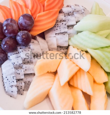 Variety of fresh fruit,Colorful fruit platter with watermelon, cantaloupe, grapes, oranges, Dragon fruit and mint - stock photo