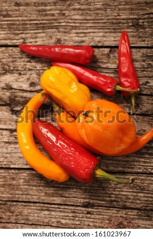 Variety of fresh peppers or capsicum including sweet bell peppers, hot chilli peppers and jalopeno lying on a rustic wooden surface, high angle view