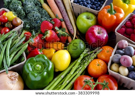 Variety of fresh raw organic fruits and vegetables in light brown containers sitting on bright blue wooden background - stock photo