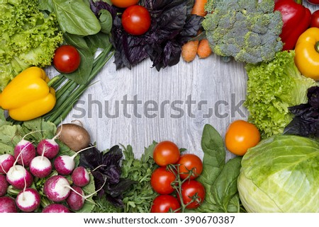Variety of fresh vegetables in the frame shape on a wood background