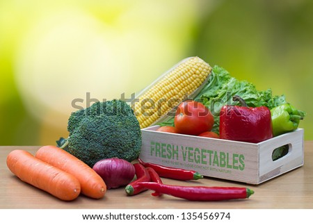 Variety of fresh vegetables in wooden box on wood table - stock photo