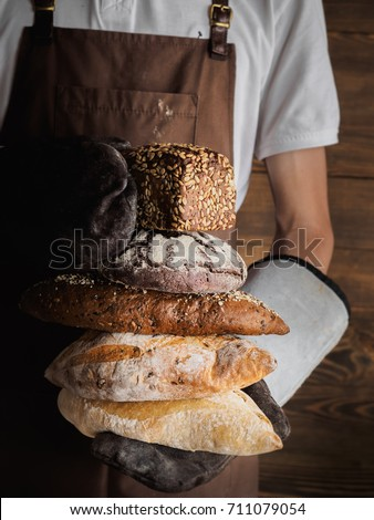 Variety of freshly baked breads in a young bakers hands. Hipster nordic baker with rye, wholewheat and white bread close up.