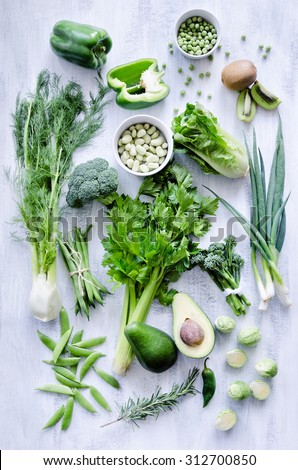 Variety of green vegetables produce on rustic white background from overhead, broccoli, celery, avocado, brussel sprouts, kiwi, pepper, peas, beans, lettuce flat lay series