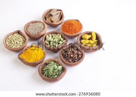 Variety of Indian spices in diyas on white background - stock photo