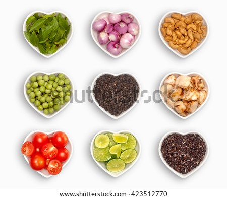 variety of ingredients in a heart shaped bowl, isolated on white Basil, shallot, cashew nut, pea eggplant, black pepper, galangal, cherry tomato, brown rice, lime