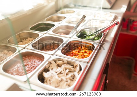 Variety of ingredients, sauces, spices and salads in a food bar. - stock photo