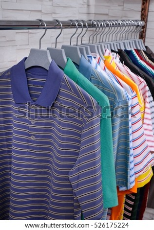 Variety of men's clothes shirts on hangers at store