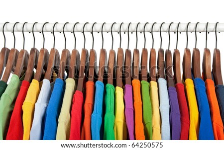 Variety of multicolored casual clothes on wooden hangers, on white background. - stock photo