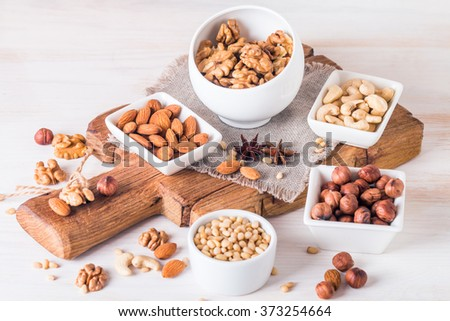 Variety of nuts: almonds, walnuts, hazelnuts cashews and pine nuts in wooden bowls on white wooden background - stock photo