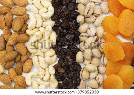 Variety of nuts and dried fruits arranged in lines. A background