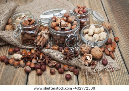 Variety of nuts: walnut, hazelnut, hazelnuts, peanuts, pine nuts and other with spices on a wooden background - stock photo