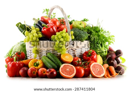 Variety of organic vegetables and fruits in wicker basket isolated on white - stock photo
