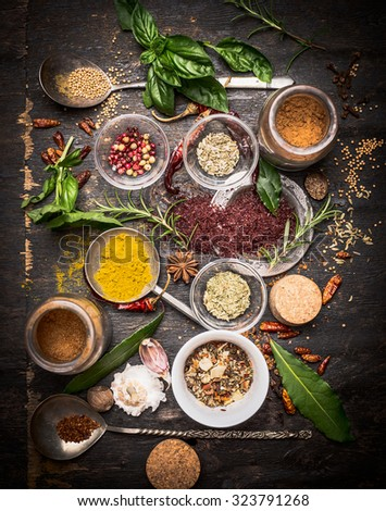 variety of oriental herbs and spices: Acetic tree, curry powder, paprika, cayan pepper, sira,Bay leaf on spoons and bowls, top view.  national cuisine  and cooking concept. - stock photo