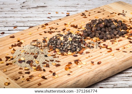 Variety of pepper including ground, crushed, whole peppercorns and red pepper flakes on wooden background - stock photo